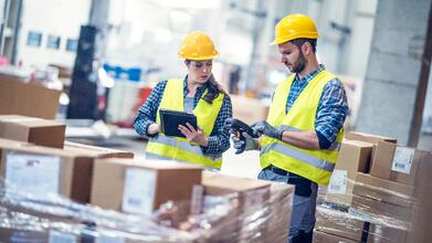 Man-and-woman-inspecting-boxes-in-a-warehouse-918699076_6013x3382